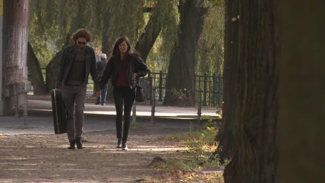 vídeos y material grabado en eventos de stock de ms couple walking on street and holding hands / berlin, germany - guitarra