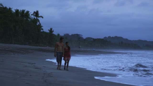 couple walking on the beach holding hands - 恋に落ちる点の映像素材/bロール