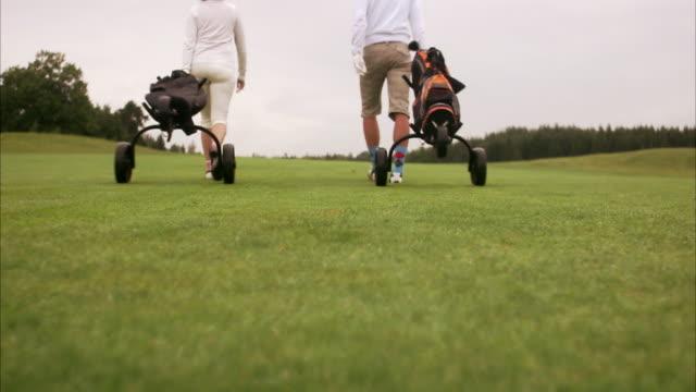 vidéos et rushes de a couple walking on the golf course sweden. - couple d'âge moyen