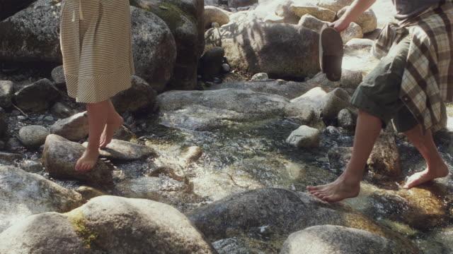 WS PAN ZO SLO MO Couple walking on water rocks / Squamish, British Columbia, Canada