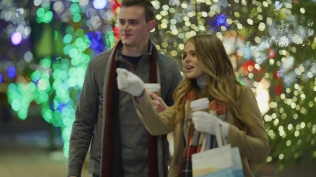 couple walking outdoors during christmas carrying shopping bags then window shopping / provo, utah, united states - provo stock videos & royalty-free footage