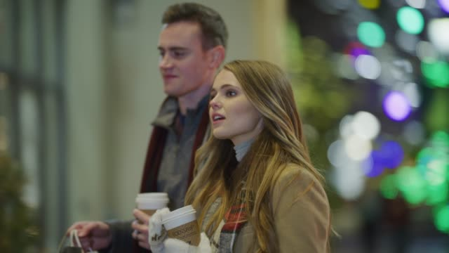 Couple walking outdoors during Christmas then entering doorway of retail store / Provo, Utah, United States