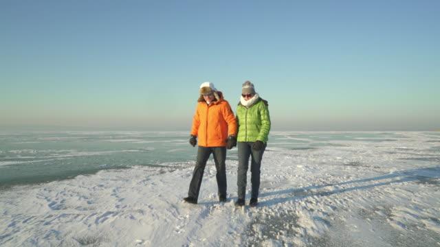 couple walking over frozen lake in winter - skijacke stock-videos und b-roll-filmmaterial