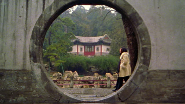 couple walking past circular doorway with building in background / summer palace, beijing, china - doorway stock videos and b-roll footage