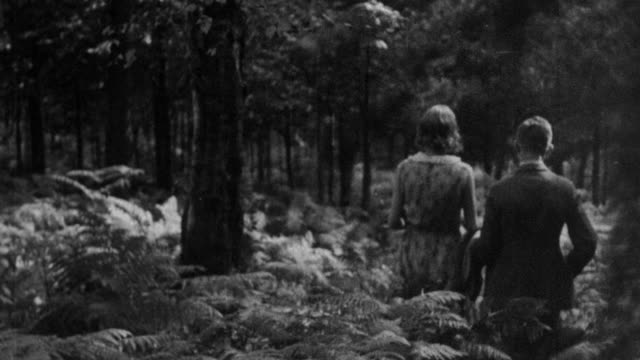 1930 montage a couple walking through a wooded area / united kingdom - 1930 stock-videos und b-roll-filmmaterial