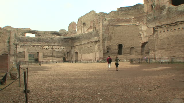 ws couple walking through baths of caracalla / rome, italy   - baths of caracalla stock videos and b-roll footage
