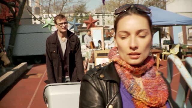 stockvideo's en b-roll-footage met ts ms couple walking through flea market, new york city, new york, usa - rommelmarkt