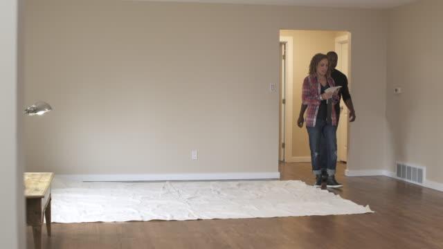 vídeos de stock e filmes b-roll de couple walking through new home, looking at colour swatches, panning right. - pano de protecção