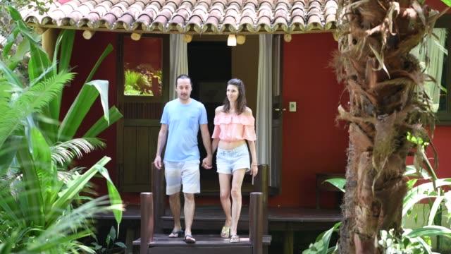 couple walking together holding hands on holiday - coppia di adulti di mezza età video stock e b–roll