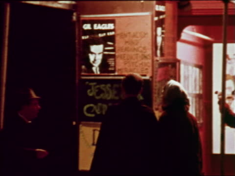 1969 couple walking toward entrance of nightclub/bar at night / greenwich village, nyc / industrial - anno 1969 video stock e b–roll