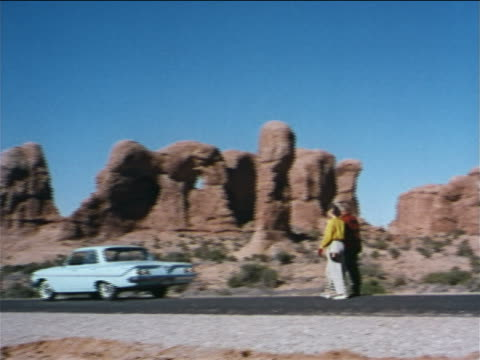 vídeos y material grabado en eventos de stock de 1962 couple walking towards car on road in southwestern us / rock formations in background / industrial - 1962