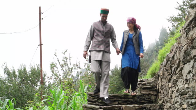 Couple walking towards the camera in a rural village setting talking and smiling and walking down steps holding hands
