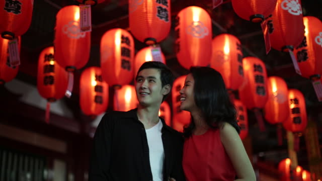 vídeos de stock e filmes b-roll de ms couple walking under red lanterns at night - vida noturna