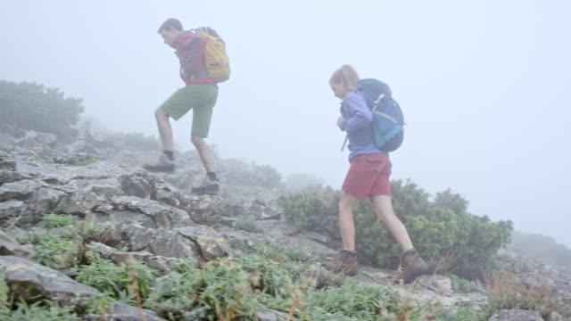 Paar lopen op een mistige berg met hun twee vrienden