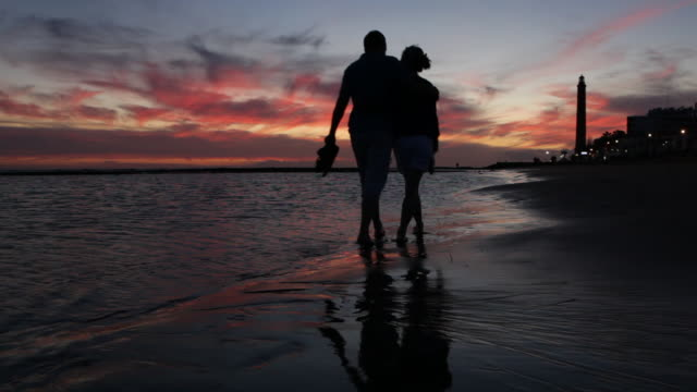 couple walking up beach in sunset. - spain stock videos & royalty-free footage