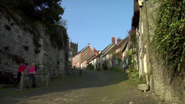 LA WS Couple walking up Gold Hill past cottages / Shaftesbury, England