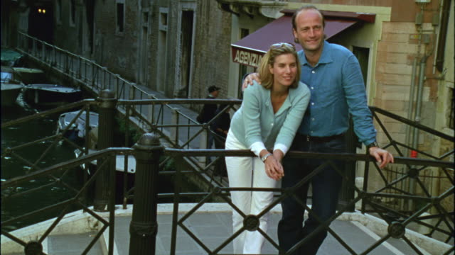HA WS Couple walking up steps of footbridge over canal and looking at view / Venice, Italy