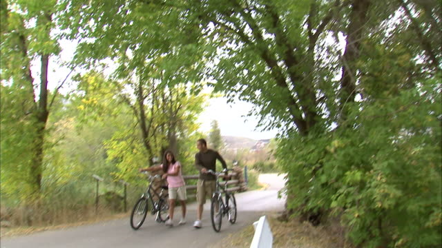 ms td couple walking with bikes down tree covered bike path / provo, utah, usa - provo stock videos & royalty-free footage