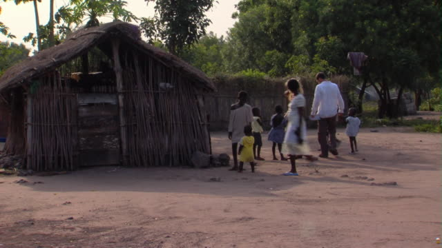 ws couple walking with group of kids next to hut, tamale, ghana - strohdach stock-videos und b-roll-filmmaterial
