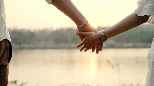 couple walking with holding hands at sunset. - holding hands stock videos & royalty-free footage