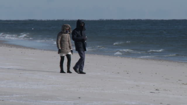A couple walks along the shore at Jones Beach New York bundled up from head to toe from the bitter cold temperatures during an arctic outbreak