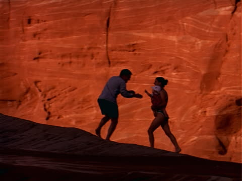 couple walks in red rock southwest setting carrying and swinging around their baby - gemeinsam gehen stock-videos und b-roll-filmmaterial