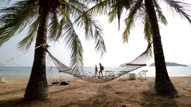 a couple walks on the beach and a hammock under palm trees - gulf of thailand stock videos & royalty-free footage