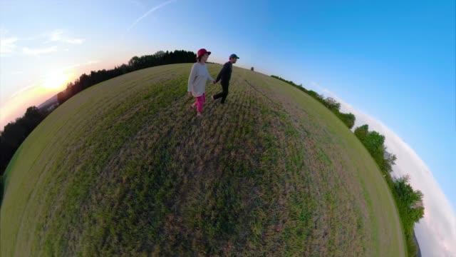 vídeos de stock, filmes e b-roll de a couple walks over a field at sunset - crepúsculo