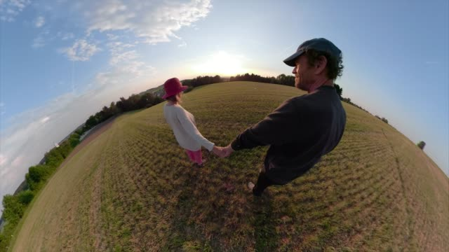 a couple walks over a field into sunset - fish eye lens stock videos & royalty-free footage