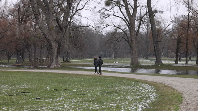 couple walks past eisbach river at english garden park while it snows at first spring weekend during the coronavirus pandemic on march 20, 2021 in... - ミュンヘン エングリッシャーガルテン点の映像素材/bロール