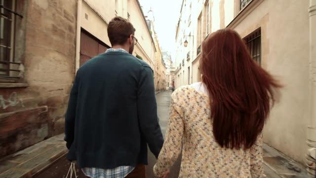 A couple walks through an alleyway in Paris.