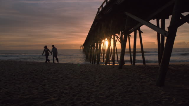 couple walks up from sunset shore holding hands (slo-mo) - wilmington north carolina stock-videos und b-roll-filmmaterial