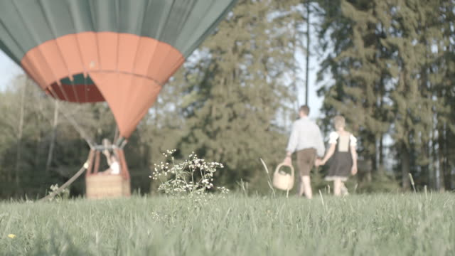 couple walks with picnic basket to hot air balloon - picnic basket stock videos & royalty-free footage
