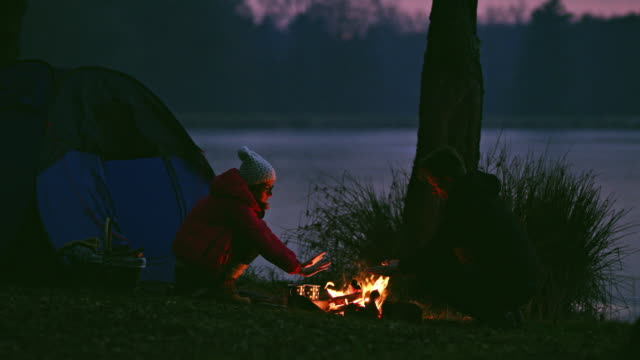 ms couple warming hands at campfire at tranquil lakeside - outdoor pursuit stock videos & royalty-free footage
