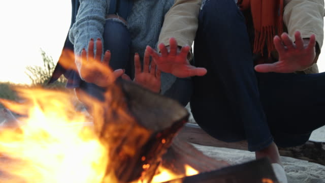 CU Couple warming hands over campfire.