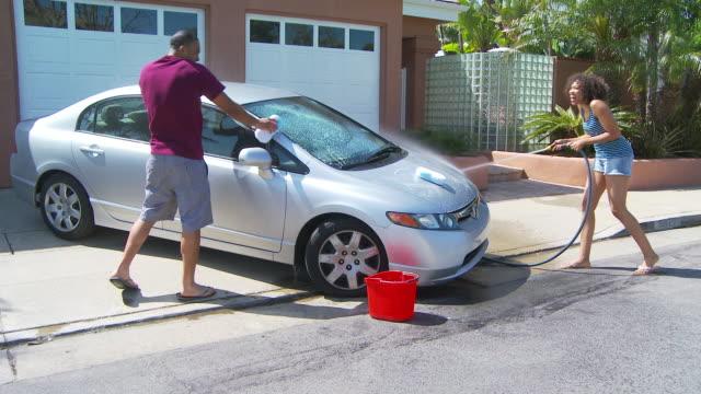 Couple washing car in driveway
