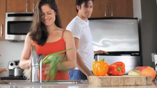 ms couple washing vegetables for cooking in kitchen, jersey city, new jersey, usa - オレンジピーマン点の映像素材/bロール