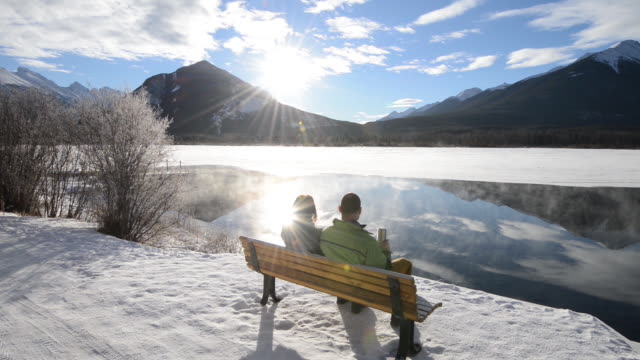 Couple watch steam rise from mountain lake in winter