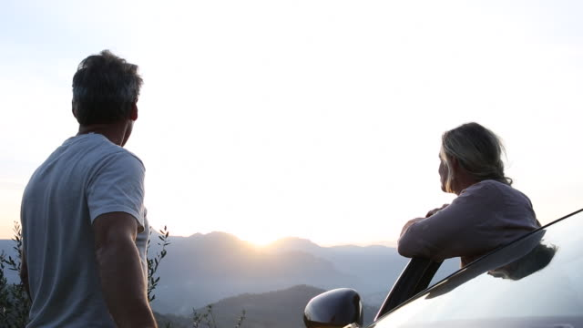 Couple watch sunrise over hills from car door, contemplative