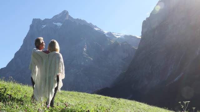 couple watch the sunrise above mountain ridge - shawl stock videos & royalty-free footage