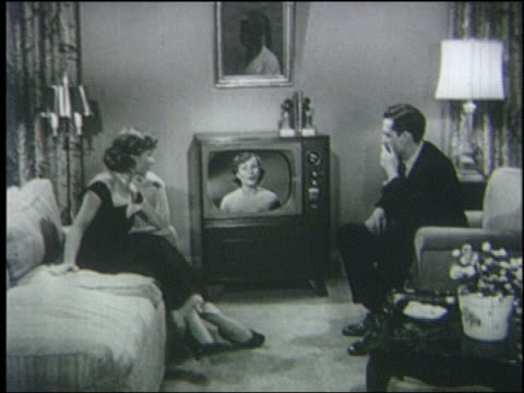 vídeos de stock, filmes e b-roll de b/w 1950 couple watches television in living room / man smokes cigarette - 1950