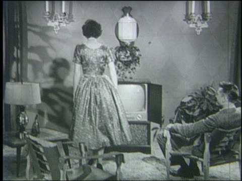 b/w 1950 couple watches television in living room / woman turns it off + closes cabinet doors - anno 1950 video stock e b–roll