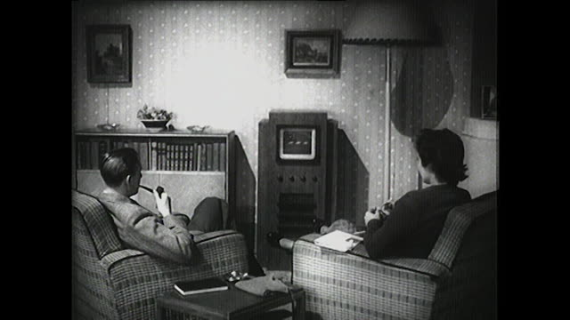 b&w - couple watches tv and throws something at it; 1950 - living room stock videos & royalty-free footage