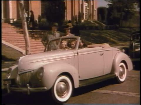 1939 couple watches + waves as three teen girls drive away in ford convertible - 1939 stock videos and b-roll footage