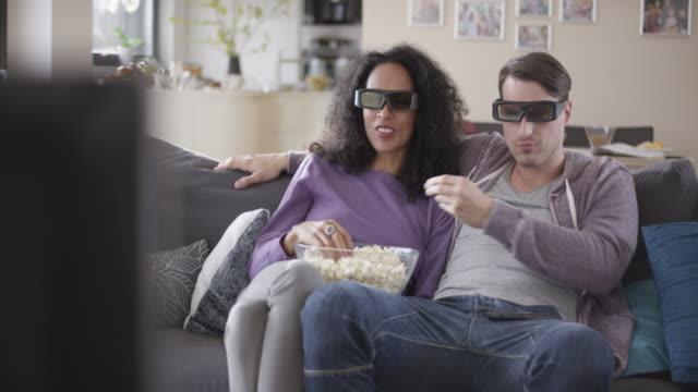 vídeos de stock, filmes e b-roll de casal assistindo tv 3d e comendo pipoca - óculos de terceira dimensão