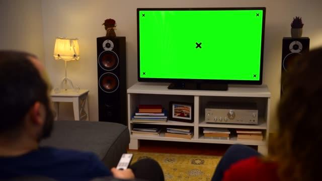 vídeos y material grabado en eventos de stock de pareja viendo croma tecla pantalla verde tv en casa - watching tv