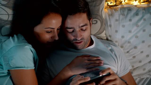 couple watching common photos on smartphone - pyjamas stock videos & royalty-free footage