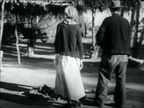 vidéos et rushes de view couple watching fully loaded car pulling into migrant worker camp - 1936