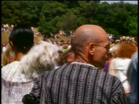 VIEW couple watching hippies dancing at outdoor concert / woman holds dog man bald