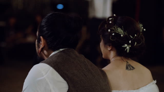 Couple watching movie at wedding party.